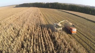 Aerial slow motion shot of combine harvester and truck gathering crops in the field. Harvest season