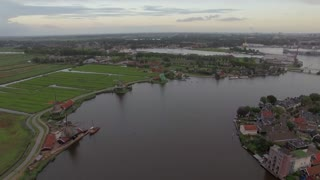 Aerial - Township with old windmills, river with sailing boat and green fields, Netherlands