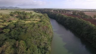 Aerial view of Mauritius nature. Narrow river with green forested banks. Farmlands on one side and road on another one