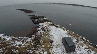 Aerial view of minivan standing by waterside with unfinished bridge with following view to the Rabocheostrovsk, township on the White Sea coast near Solovki