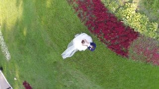 Aerial view of newly wedded couple in green park with following cityscape of Moscow, Russia