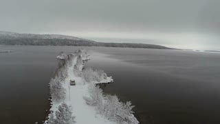 Aerial view of offroader driving slowly along the narrow snowy island road in the lake or river. Winter landscape with tree covered mountains in the distance