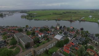Aerial view of river flowing through the township with windmills and green fields, Netherlands