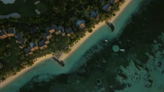 Aerial view of the ocean coast with houses alongside. Tropical island with white sand beach. Vacation in Mauritius