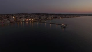 Aerial view of touristic boat leaving the pier and sailing in quiet sea in the dusk. Sea travel during vacation on resort in Thessaloniki, Greece