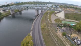 Aerial view of truck and cars driving along the road under the railway bridge over the river in the city