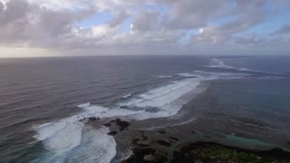 Aerial view of water line of seas that do not mix and rugged coast line against blue sky with clouds, Indian Ocean, Mauritius Island