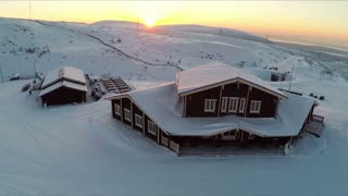 Aerial view of wooden buildings on the area of winter ski centre in Khibins, snowfields and hills at sunset. Kola Peninsula, Russia