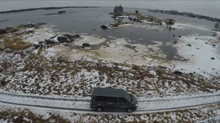 Aerial winter shot of a car driving in severe area. White Sea coast in winter with view to old wooden house and Rabocheostrovsk, township near Solovki