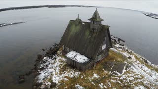 Aerial winter shot of solitary house on the waterside with following view to the sea and coastal town Rabocheostrovsk, located near Solovetsky Islands