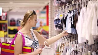 Attractive young mother shopping for childrens clothes in a retail clothing store viewing items on a rack