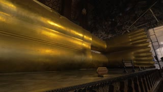BANGKOK, THAILAND - NOVEMBER 02, 2015: Panning shot of statue of reclining Buddha in Wat Pho temple. Giant figure represents the entry of Buddha into Nirvana and the end of all reincarnations
