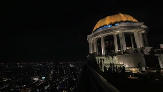 BANGKOK, THAILAND - NOVEMBER 1, 2015: In a large round building climb the stairs people. Seen evening city with busy streets and roads. Thailand is visited by more than 26 million turists annually
