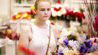 Beautiful young lady buying fresh flowers in a store or market choosing blooms for her decor at home