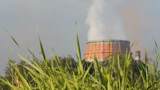 Big smoking factory chimney with green grass in foreground. Ecology concept