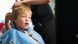 Boy unwilling to wear a cape and taking it off, while hairdresser cutting his hair