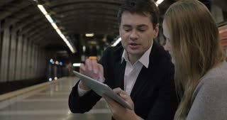 Business people are sitting in the metro station holding tablet PC and discussing the case they see there.
