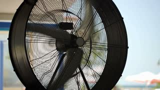 Close-up shot of a big working ventilator with its blades rotating rather slowly. Cooling and air ventilation