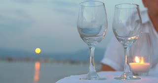Close-up shot of a man pouring white wine into two glasses standing on the table with candle in outdoor restaurant on the beach