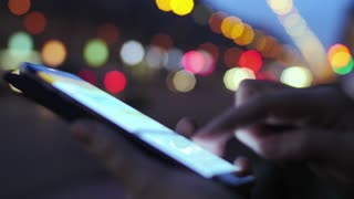 Close-up shot of a woman typing message on smart phone at the roadside in the evening. Colorful blurred city and traffic lights in background