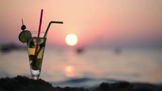 Close-up shot of  mojito cocktail with straws on beach, sunset and sea in background