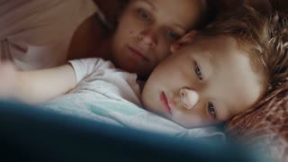 Close-up shot of mother and son in bed. Boy playing game on pad, mother helping him with advice. Bedtime entertainment