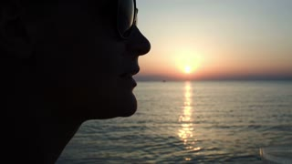 Close-up shot of young woman in sunglasses drinking beer on the beach during sunset