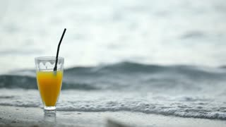 Cocktail with straw on beach with sea waves washing shore and glass. Summer vacation