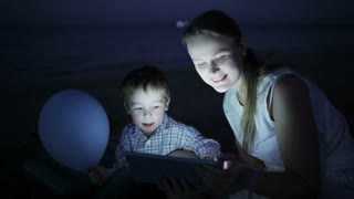 Cute kid and his mother on the beach in the light of pad screen at night