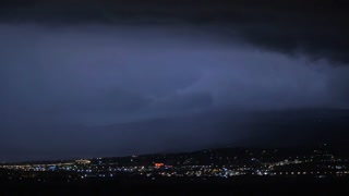Dark sky flashing with lightnings during the night storm over the city