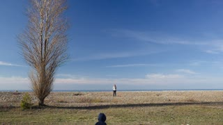 Distant view of a little boy running to his mother. Scenic landcape around with lonely tree, blue sky and sea