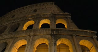 Dolly and low angle shot of illuminated Coliseum at night, the world famous ancient amphitheater in Rome, Italy