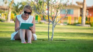 Dolly shot of beautiful woman wearing sunglasses sitting barefoot on a lawn in the shade of a tree with a laptop computer on her lap