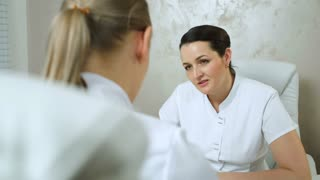 Dolly shot of woman cosmeticians talking. Young cosmetician consulting an experienced colleague