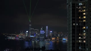 Downtown of Hong Kong during every night light show Symphony of Lights. Illuminated skyscrapers on waterside, ship sailing in quiet harbour