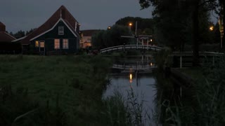 Evening rural scene with house in Dutch village and bridge across the pond