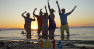Family celebrating New Year or Christmas on the beach at sunset. Happy people dancing in sea water, colorful 2016 number in foreground