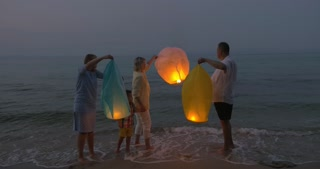 Family with mother, child and grandparents flying paper lanterns at the seaside in the evening. They waving hands as it flying away in clear sky