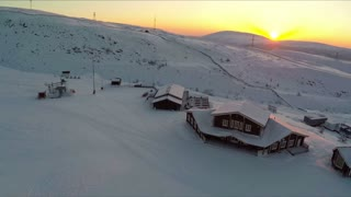 Flying over the area of ski centre located in Khibins. Wooden buildings, vast snowfields and hills at golden sunset. Russian north