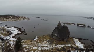 Flying over the old wooden monastery located on the edge of the coast with following distant view of Rabocheostrovsk, township near Solovki, Russia. Winter shot