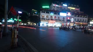 HANOI, VIETNAM - OCTOBER 28, 2015: Timelapse of night city Quang truong Dong Kinh Nghia Thuc, seen busy road with passing cars, motorcycles and cyclists, buildings with advertising signs. Vietnam is