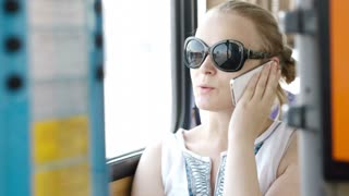 Happy attractive young woman wearing sunglasses talking on her smartphone and smiling with delight while travelling by bus