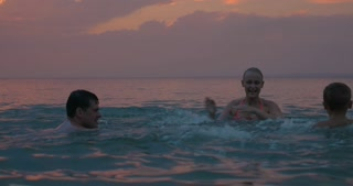Happy family of three enjoying evening in the sea. The bathing and fooling around with splashing water on each other