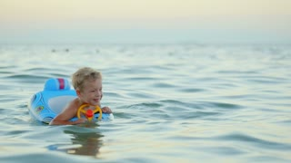 Happy little boy with rubber ring made as car swimming in sea. Summer vacation