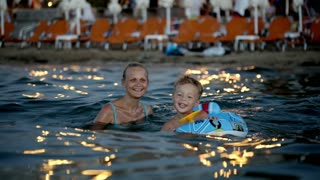 Happy mother and little son swimming in sea near the shore in the evening. Boy using rubber ring made as car