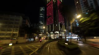 HONG KONG - NOVEMBER 09, 2015: Timelapse shot of a ride by double-decker tram along the street of night illuminated city. View from upper deck