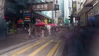 HONG KONG - NOVEMBER 09, 2015: Timelapse shot of people crowd walking on the street with stores and market. Vendors and shop banners outdoor