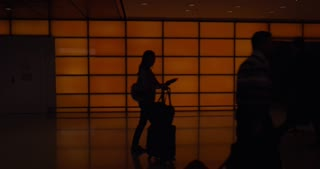 HONG KONG - NOVEMBER 8, 2015: People with baggage and luggage carts walking in airport terminal. Black silhouettes in dark corridor against orange wall