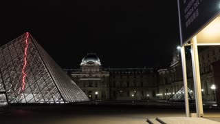 Hyperlapse shot of few people walking outside the Louvre and illuminated glass Pyramid at night. World famous art museum in Paris, France