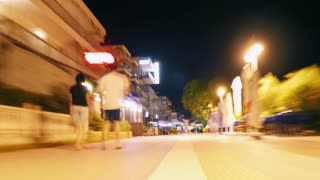 Hyperlapse shot of going along crowded sidewalk in resort town at night. Vibrant street is brightly illuminated with lanterns and lights of cafes and stores